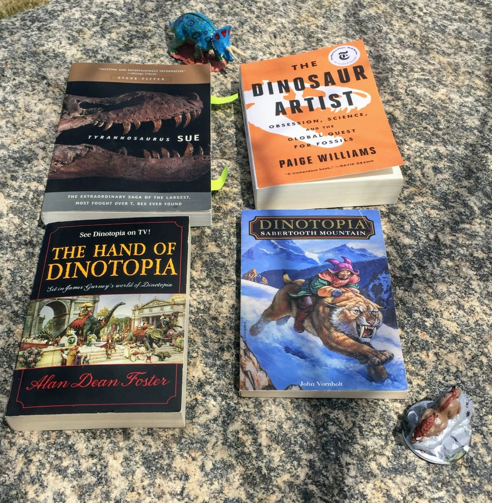 "Four books sitting on a grey granite rock. The top left is ""Tyrannosaurus Sue,"" which has a black cover and a brown tyrannosaur skull on it. The Top right is ""The Dinosaur Artist"" which has an orange cover with a white tyrannosaur skull on it. Bottom left is ""The Hand of Dinotopia"" with a black cover and illustrations of a dinosaur-inhabited city on it. The bottom right book is ""Sabertooth Mountain,"" which has a boy in a purple hat riding a sabertooth down a snow-covered mountain on its cover."