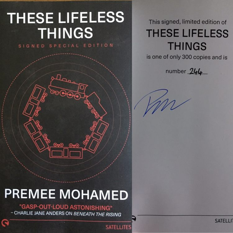 """The cover for Premee Mohamed's """"These Lifeless Things."""" The cover is black with white text, and a red train running in a circle in the center. Attached to the cover photo is a second photo of the interior front page, which shows Mohamed's Signature, and that the book is a limited edition copy, number 244 of 300."""