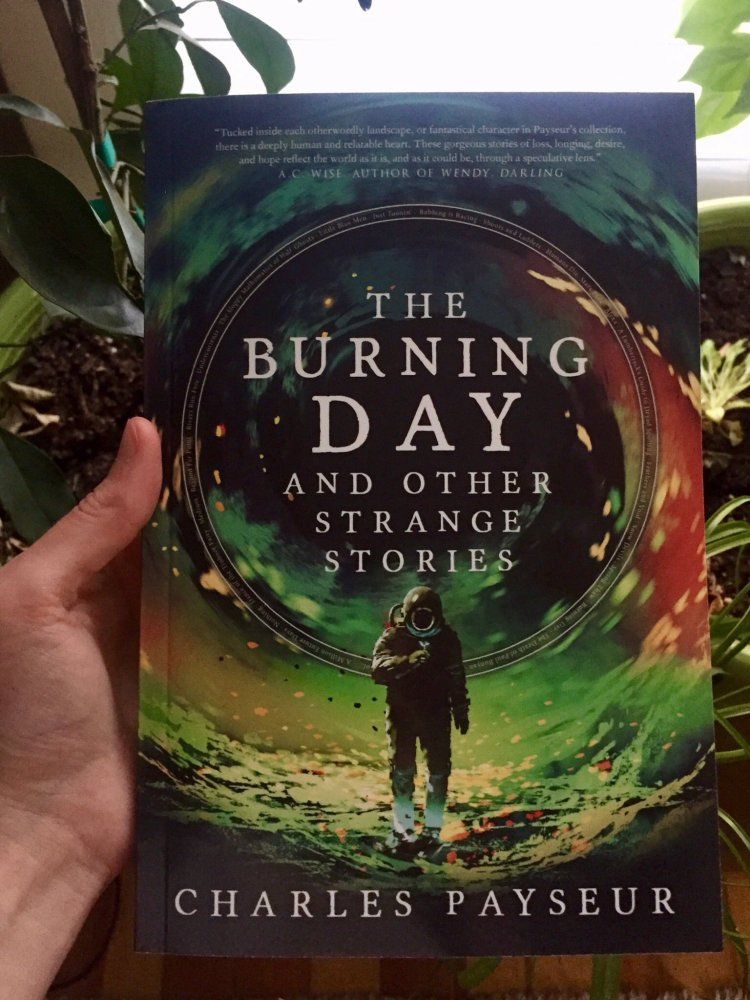 A copy of the book The Burning Day and Other Strange Stories by Charles Payseur. The cover has an astronaut figure standing beneath the title, with a green and orange ring behind them. The book is held by a white hand, in front of some plants that can be seen around the edges.