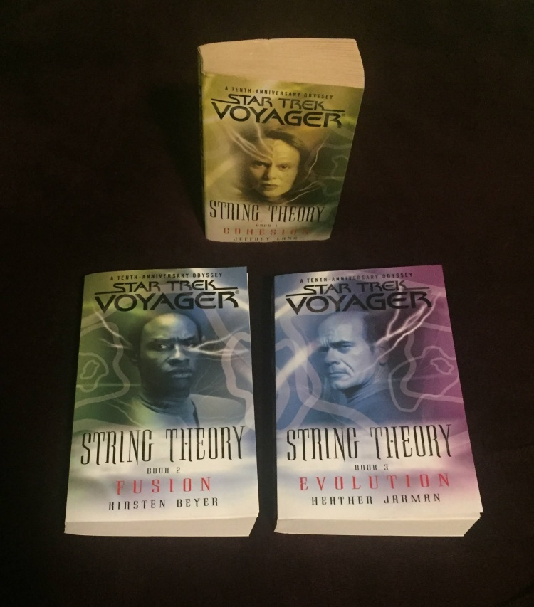 The three books from the Star Trek: Voyager String Theory trilogy sitting on a purple background. The top book has a primarily yellow cover with B'Elanna Torres on it. The other two books are sitting below the first one. The second book is green and blue with Tuvok on the cover, and the third book is blue and purple with the Doctor on the cover.
